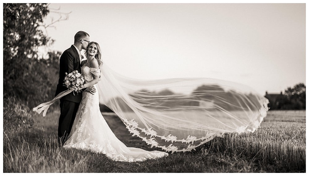 Wedding photographer at Apton Hall with brides veil blowing in the wind
